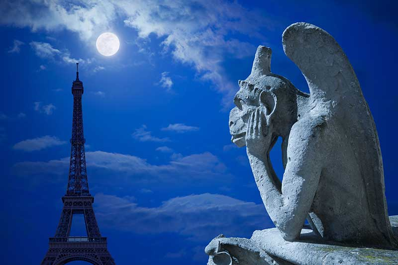 Gargoyle from Notre Dame staring at the Eiffel Tower with a full moon in the night sky.